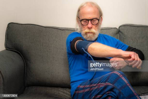 senior man putting on a cuff in preparation to take his blood pressure while sitting on a sofa in his home - johnfscott stock pictures, royalty-free photos & images