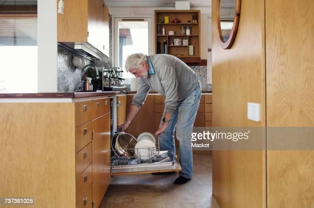 Senior man putting plates in dishwasher at kitchen