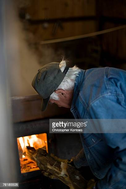 senior man putting wood into a furnace - wood burning stove stock photos and pictures
