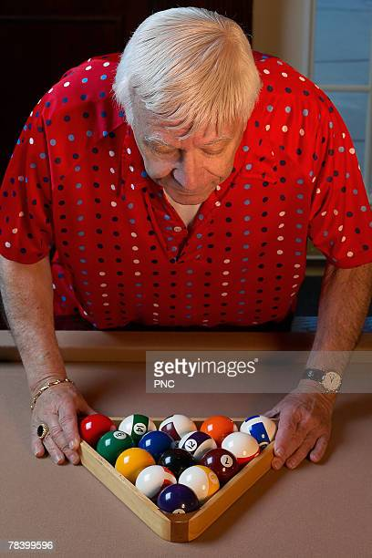 Senior man racking pool balls