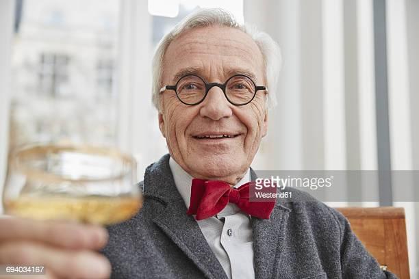 Senior man raising champagne glass