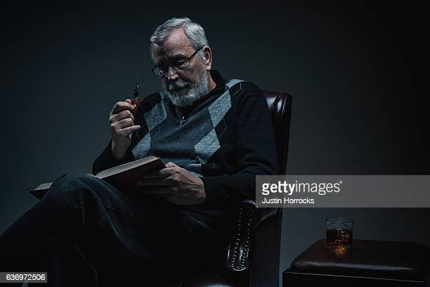 senior man reading a book in dimly lit room - pipe smoking pipe stock photos and pictures