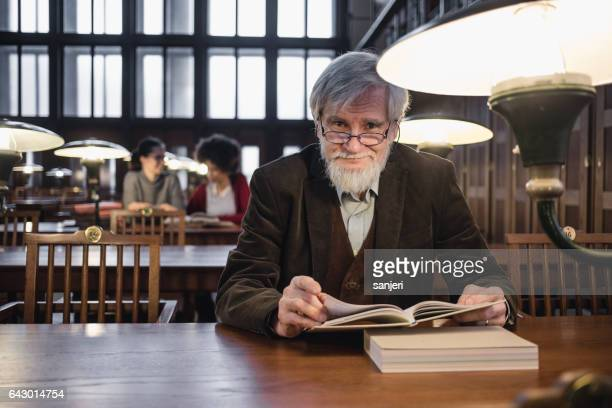 Senior man reading a book in the library and looking at camera