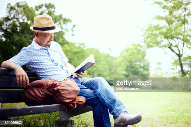 a senior man reading a book on a park bench. - park bench stock pictures, royalty-free photos & images
