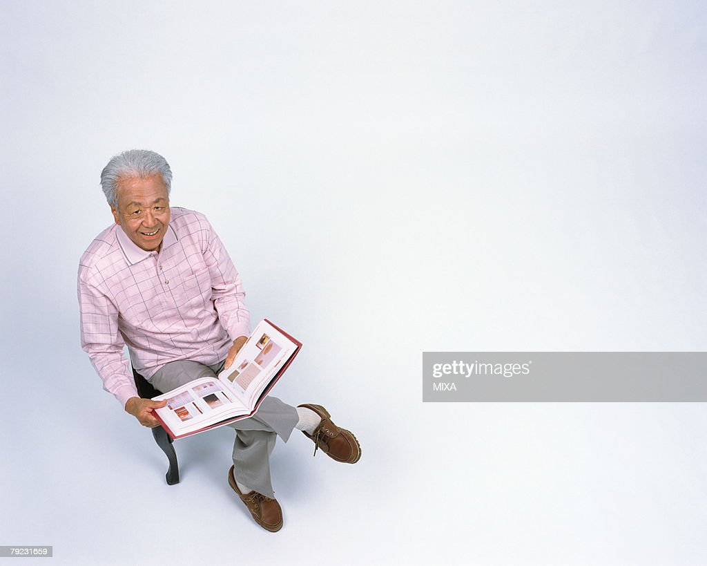 A senior man reading a book : Stock Photo