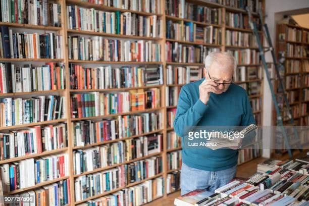 Senior man reading book against bookshelf