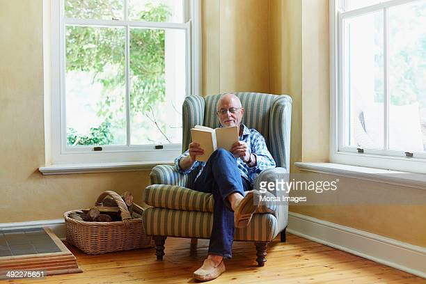 senior man reading book at home - reading stock pictures, royalty-free photos & images