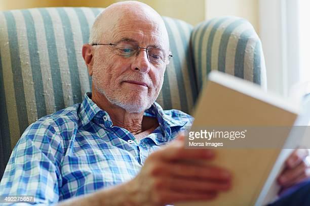 senior man reading book at home - einzelner senior stock-fotos und bilder