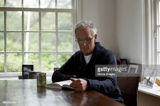 Senior man reading book in cottage