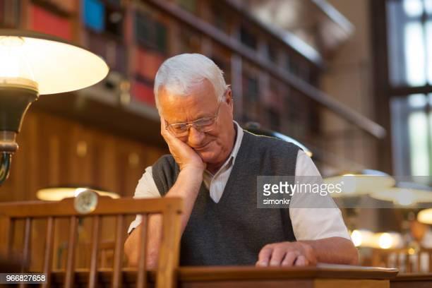 senior woman lesebuch in bibliothek - einzelner senior stock-fotos und bilder