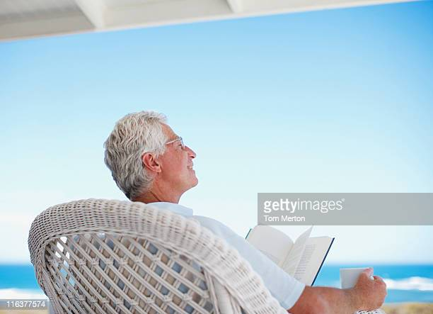 senior man reading book on beach patio - look back at early colour photography stock photos and pictures