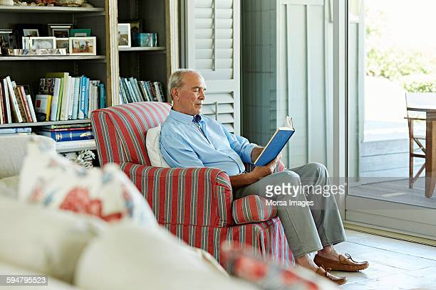 Senior man reading book on chair
