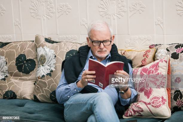Senior man reading book on couch