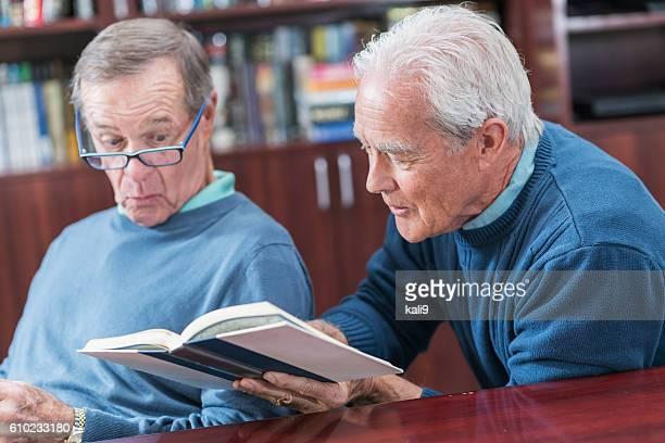 Senior man reading book, showing friend