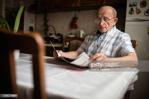 senior man reading daily newspapers at home - magazine stock pictures, royalty-free photos & images