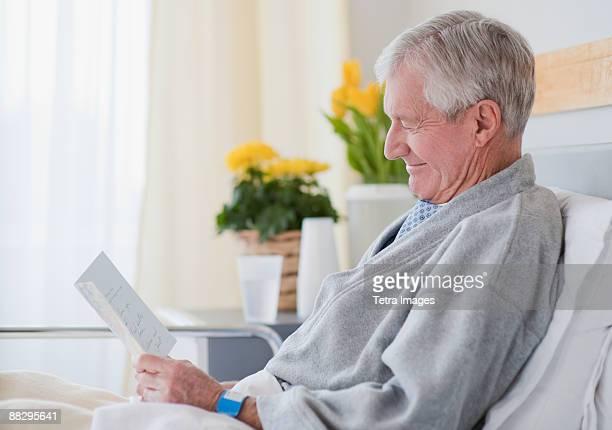 Senior man reading get well card in hospital