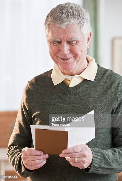 senior man reading greeting card - greeting card bildbanksfoton och bilder