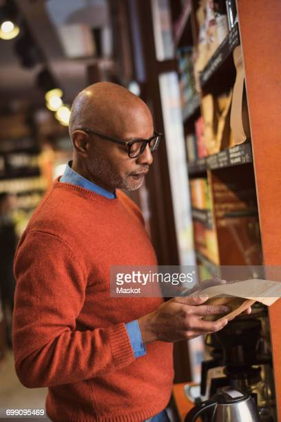Senior man reading label on food packet while shopping at store