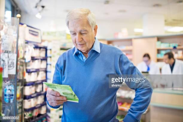 Senior man reading medicine package at pharmacy