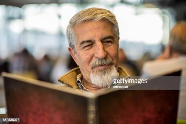 "älterer mann liest-menü im restaurant "" - warzen stock-fotos und bilder"