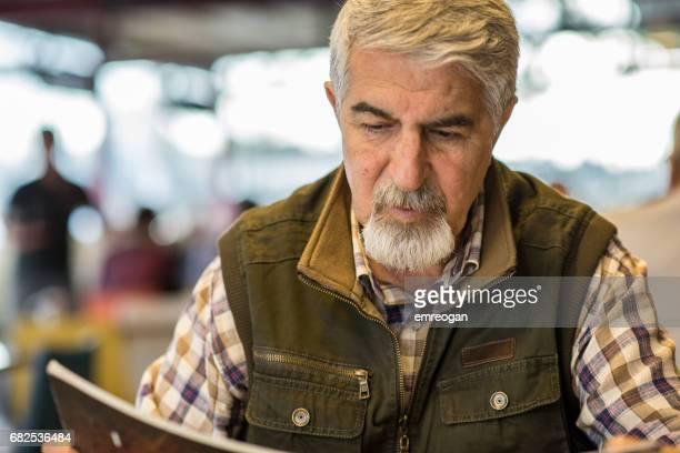 Senior Man Reading Menu in Restaurant
