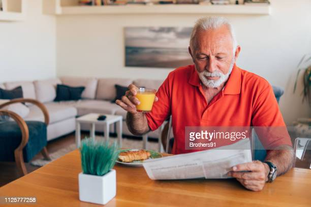 senior man reading morning newspapers - indipendenza foto e immagini stock