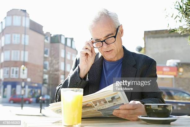 senior man reading newspaper at cafe - news not politics stock pictures, royalty-free photos & images