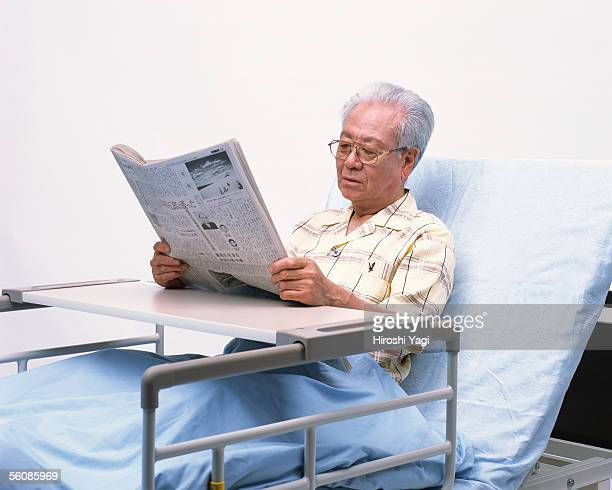 A senior man reading newspaper in a bed