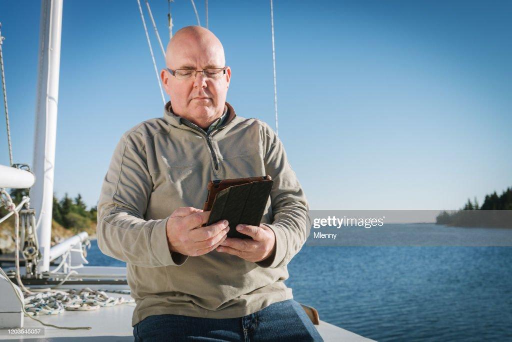 Senior Man Reading On Digital Tablet On His Sailboat : Stock Photo