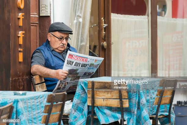 Senior man reading Sözcü newspaper at outdoor street cafe in Safranbolu, Turkey