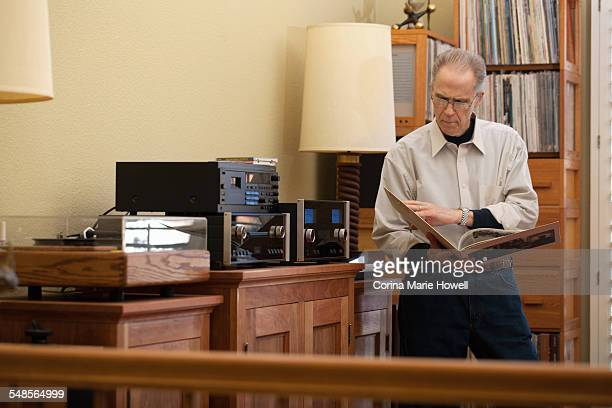 Senior man reading vinyl record cover in living room