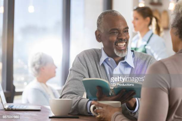 senior man reads book with wife - book club meeting stock pictures, royalty-free photos & images