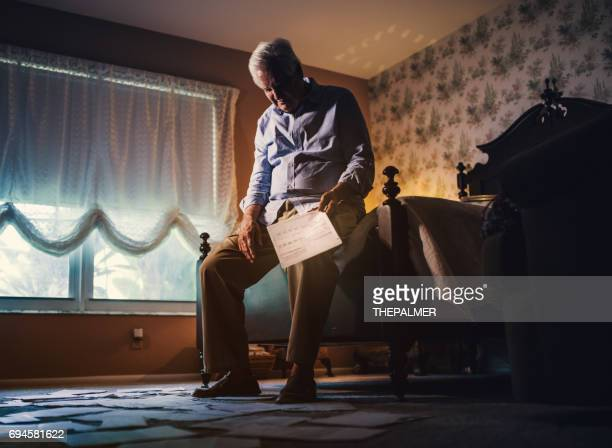 年配の男性受け取って銀行債務書類 - 経済破綻 ストックフォトと画像