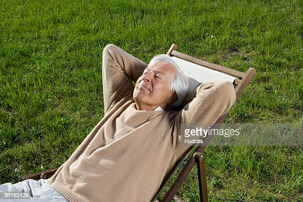 A senior man reclining in a lounge chair on a lawn