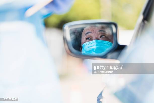 車の鏡に映るシニアマンは、コロナウイルスに対する不安を示す - ドライブスルー検査 ストックフォトと画像