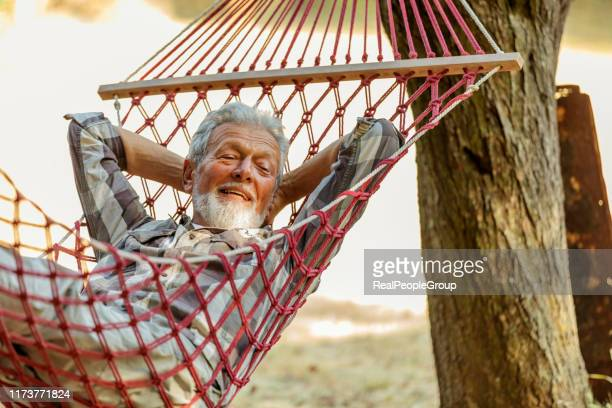 senior man relaxation in hammock - hammock stock pictures, royalty-free photos & images