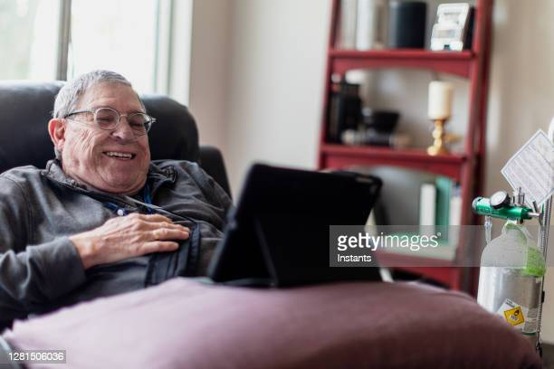 senior man relaxing and having a good time while sitting in a recliner and watching funny content on his tablet. - condition stock pictures, royalty-free photos & images