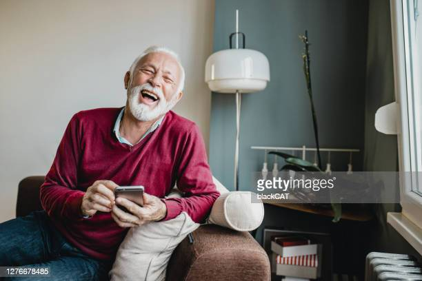 senior man relaxing at home and using mobile phone - red shirt stock pictures, royalty-free photos & images