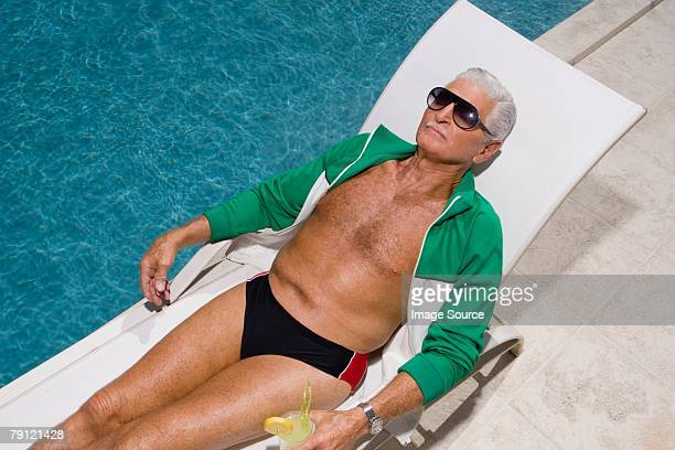 senior man relaxing by pool - zwembroek stockfoto's en -beelden