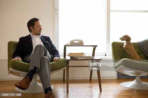 Senior man relaxing in chair at home, looking at dog