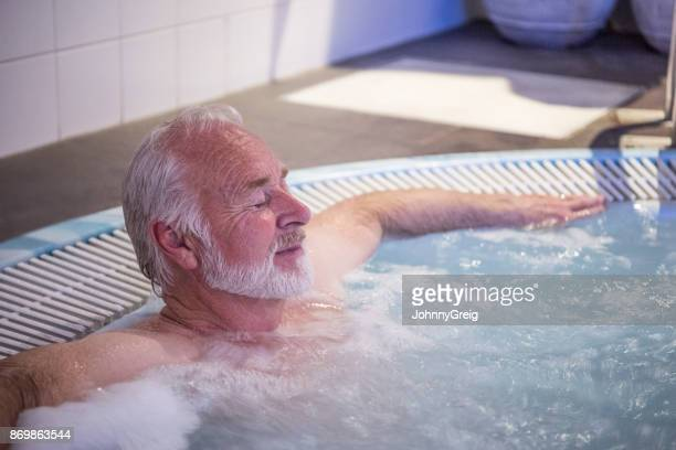 senior man relaxing in hot tub with his eyes closed - hot tub stock pictures, royalty-free photos & images