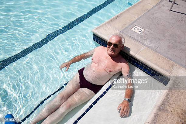 senior man relaxing in pool. - old man in speedo stock photos and pictures