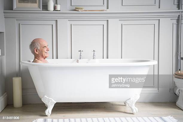 Senior man relaxing in traditional white bath smiling