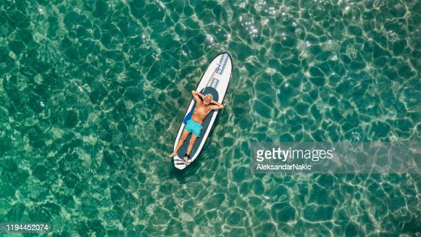 senior man relaxing on a paddleboard - one man only stock pictures, royalty-free photos & images