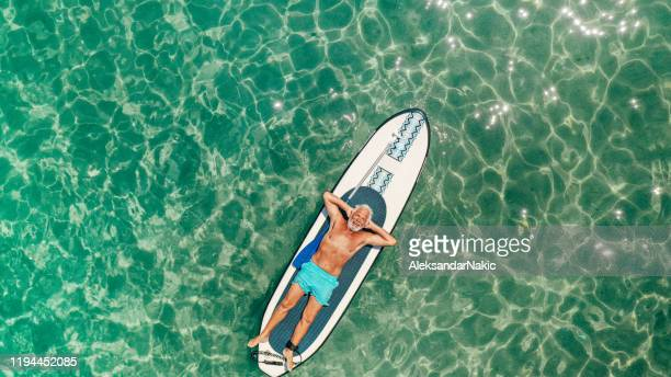 senior man relaxing on a paddleboard - lying on back stock pictures, royalty-free photos & images