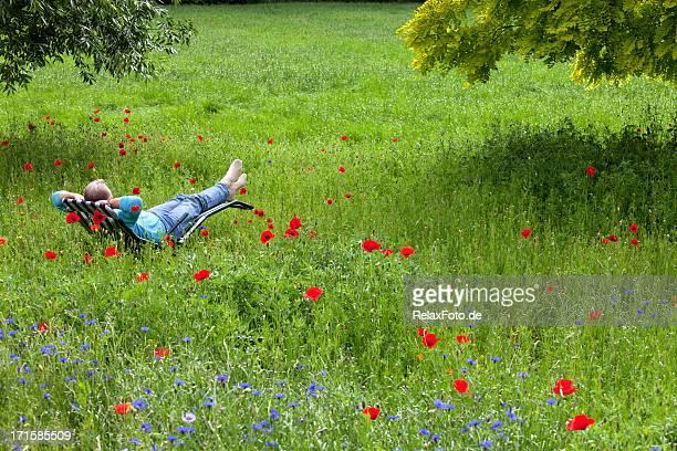 Senior man relaxing on deck chair in garden