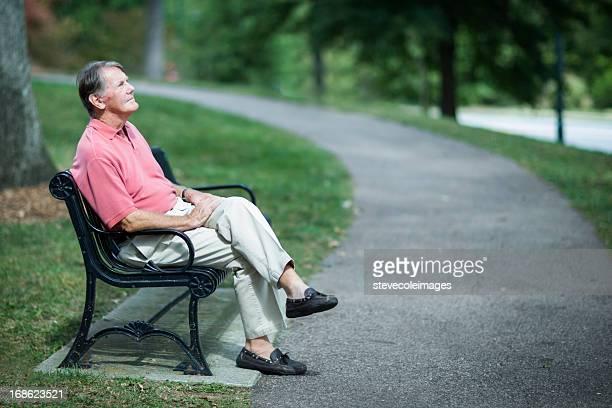 Senior Man Relaxing On Park Bench.