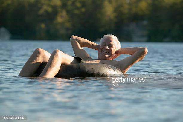 Senior man relaxing on plastic tube smiling, portrait