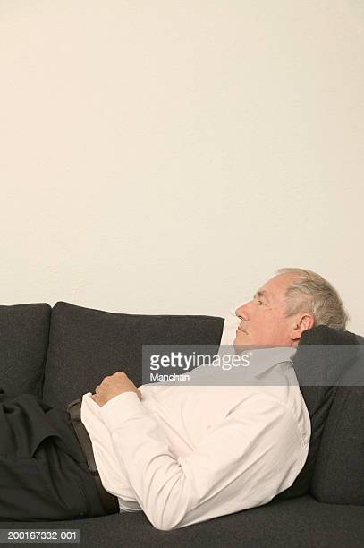 Senior man relaxing on sofa, profile, mid section