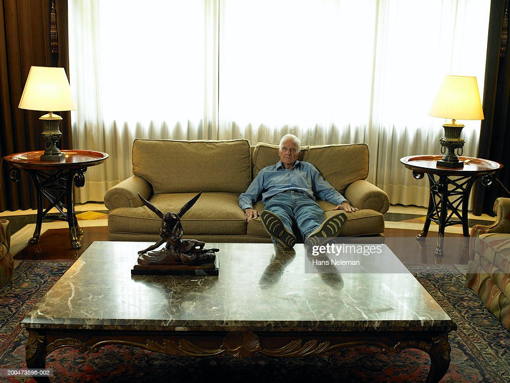 Senior man relaxing on sofa, propping feet on table : Stock Photo